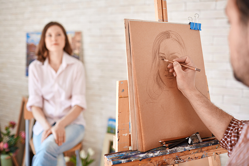 Guy drawing girl on canvas