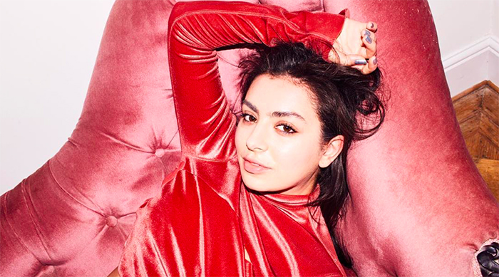 Charli XCX posing on a pink couch