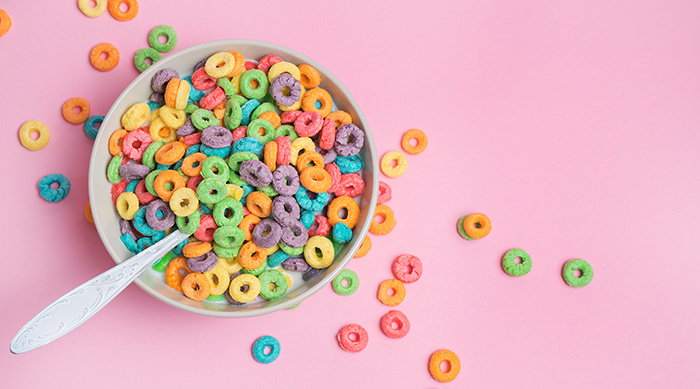 Froot Loops cereal in a bowl on a pink background