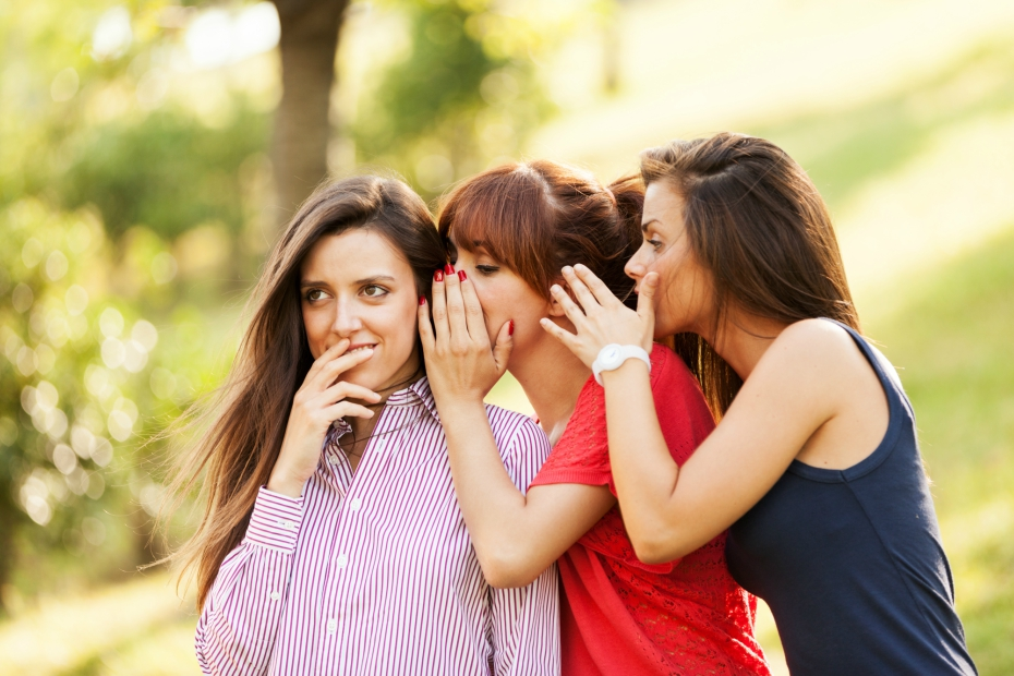 three girlfriends whisper in each others' ear while telling a secret