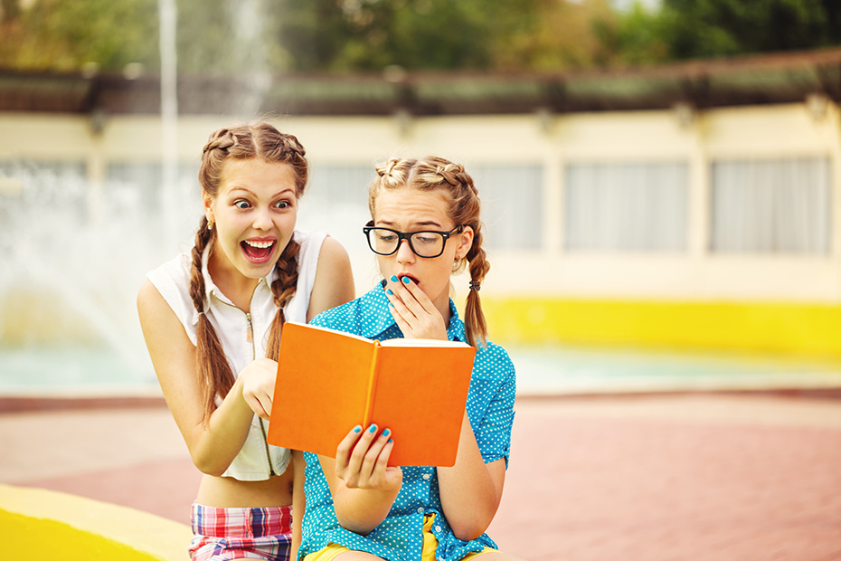 Two girls laughing and shocked reading diary/journal