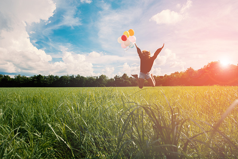 Girl jumping in a field while holding balloons