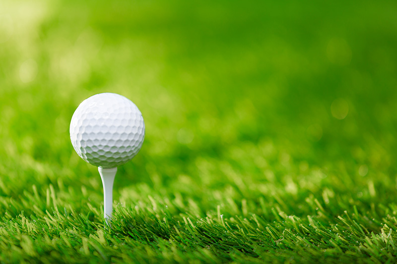 Golf ball on a white tee in the grass