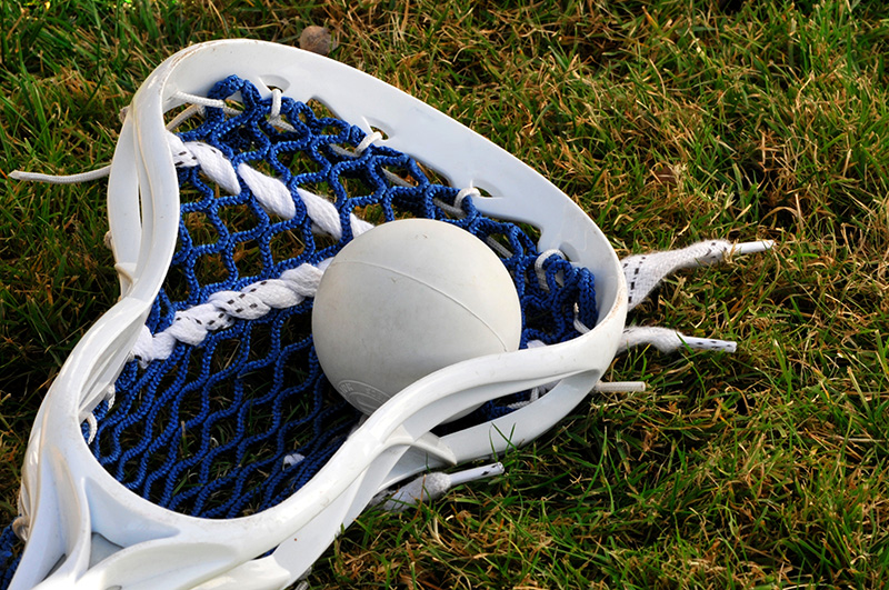 Lacrosse stick with a white ball inside laying on the grass