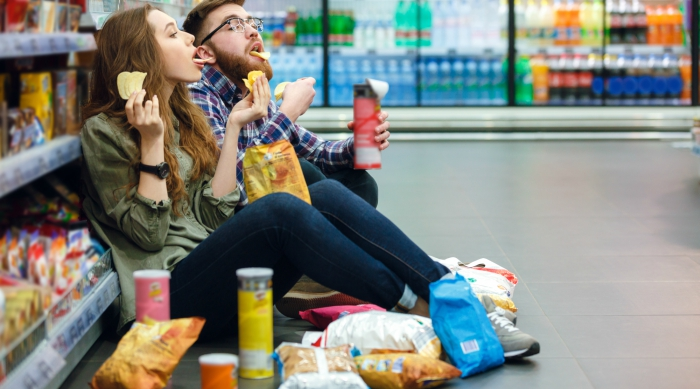 Two friends sitting on grocery store floor eating junk food