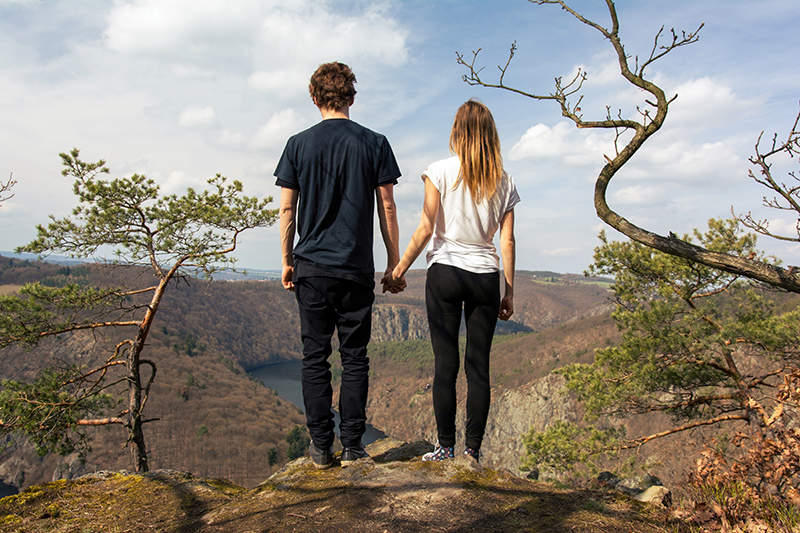 Couple holding hands while on the edge of a rock looking over nature