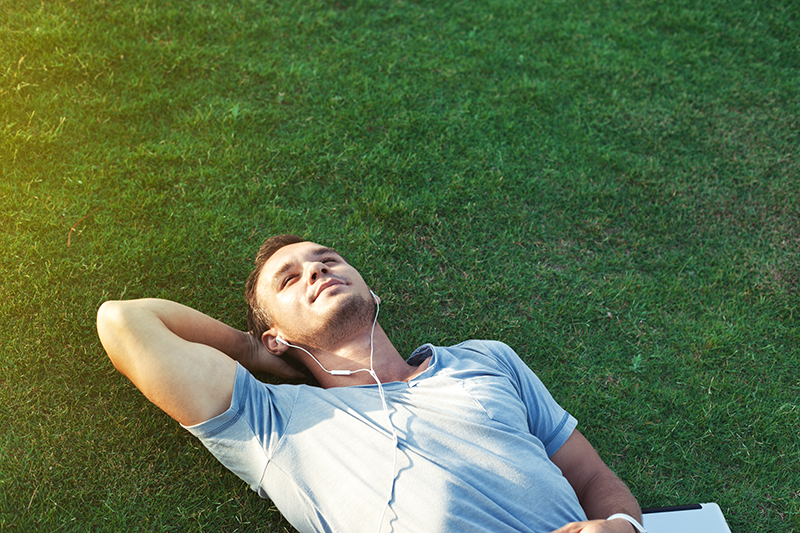 Guy laying in the grass staring up at the sky while listening to music through his headphones