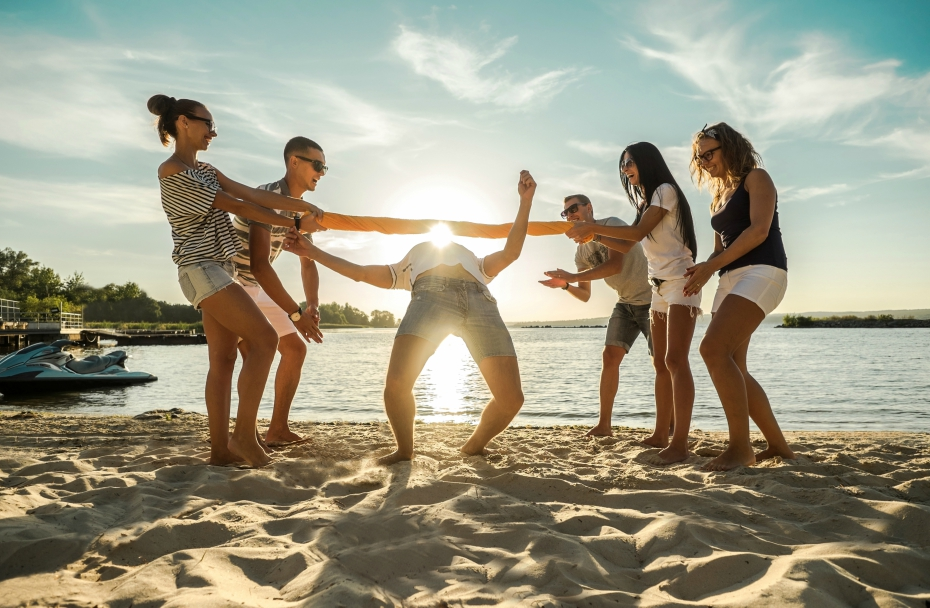 friends play games at the beach during summer