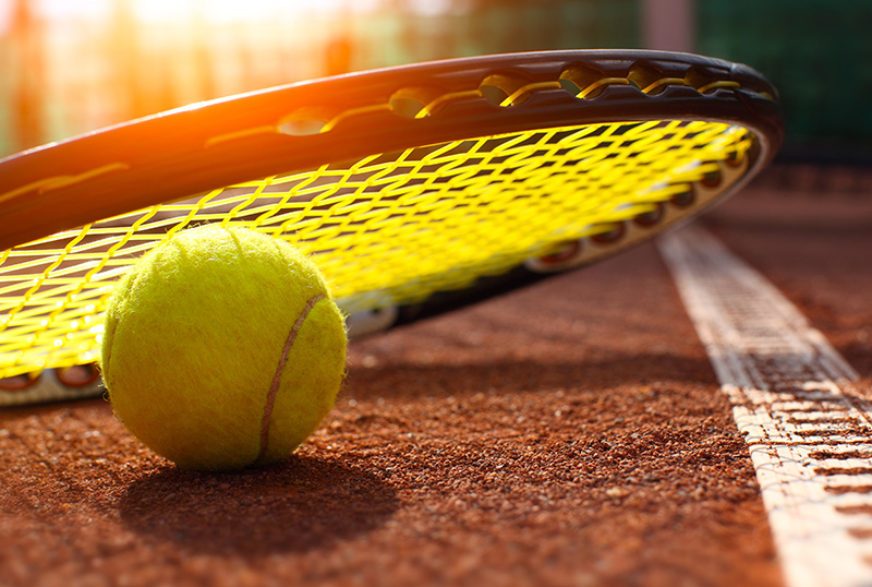 Tennis ball and racket laying on a tennis court