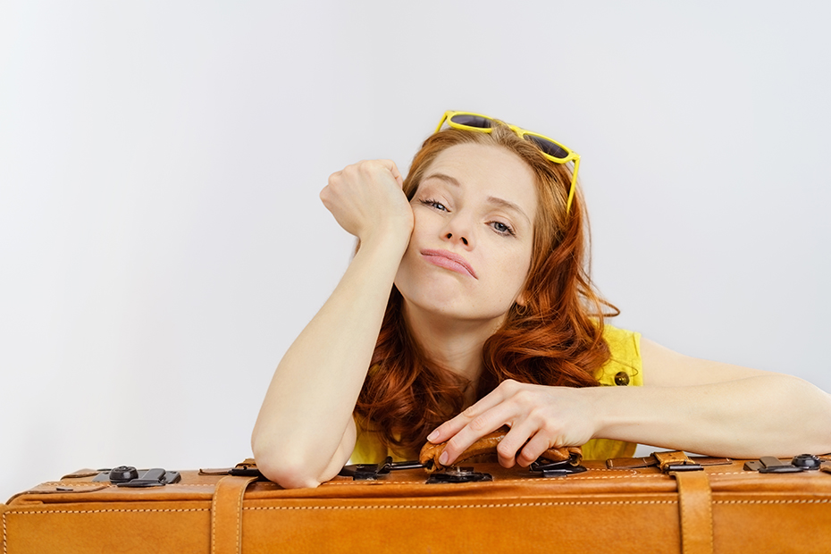 Girl bored with sunglasses and suitcase in the summer