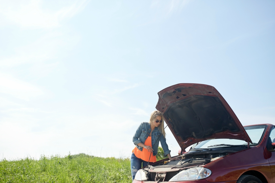 Girl trying to fix car on side of the road