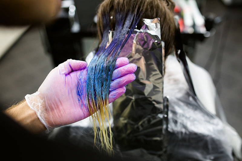 Guy dyeing girl's hair purple and blue ombre in a salon