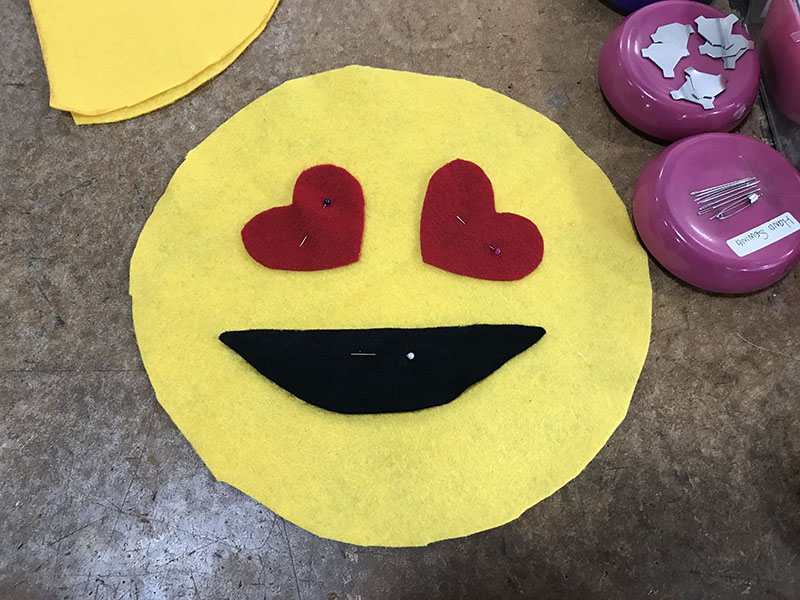 Pinning on the face of an emoji pillow