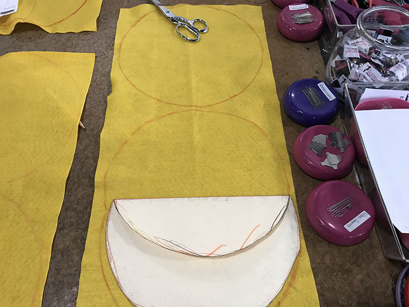 Tracing an emoji pillow template onto yellow felt