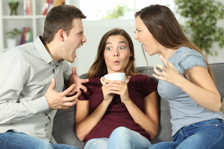 uncomfortable girl sips tea or coffee as a girl and boy fight next to her