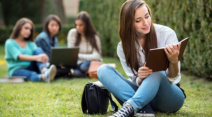 Teen girl studying in the grass
