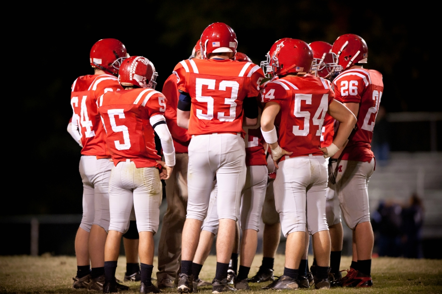 Huddle of football players during game