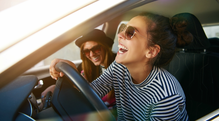 Two friends laughing while driving in a car together