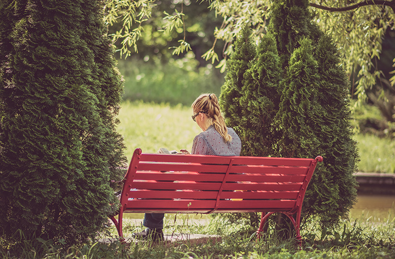 Girl reading alone on a red park bench