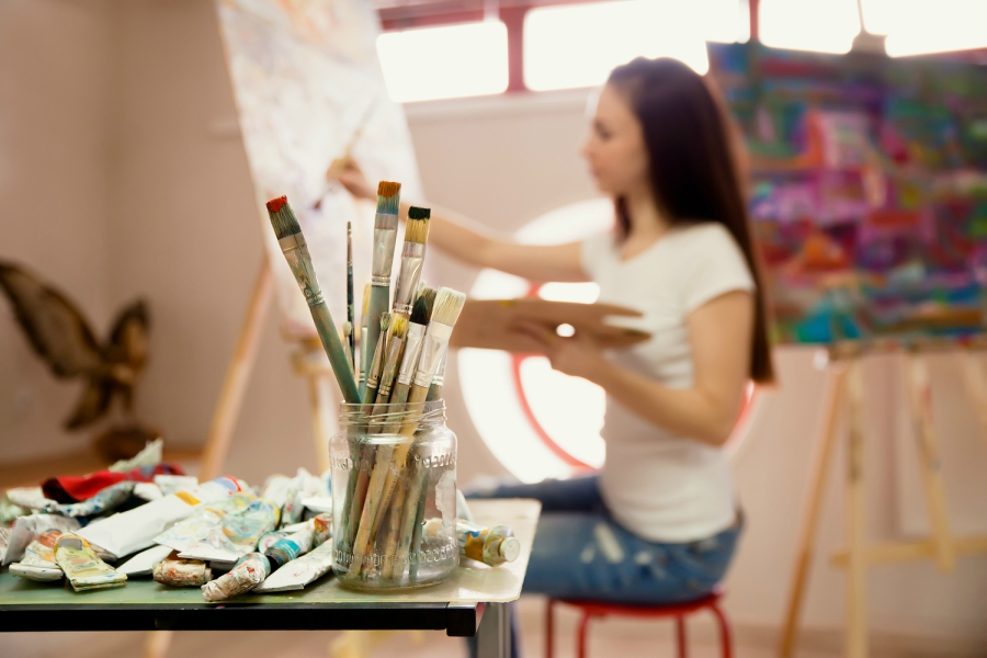 Girl painting on canvas during art class
