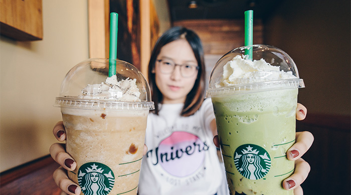 Girl holding up two big Starbucks drinks
