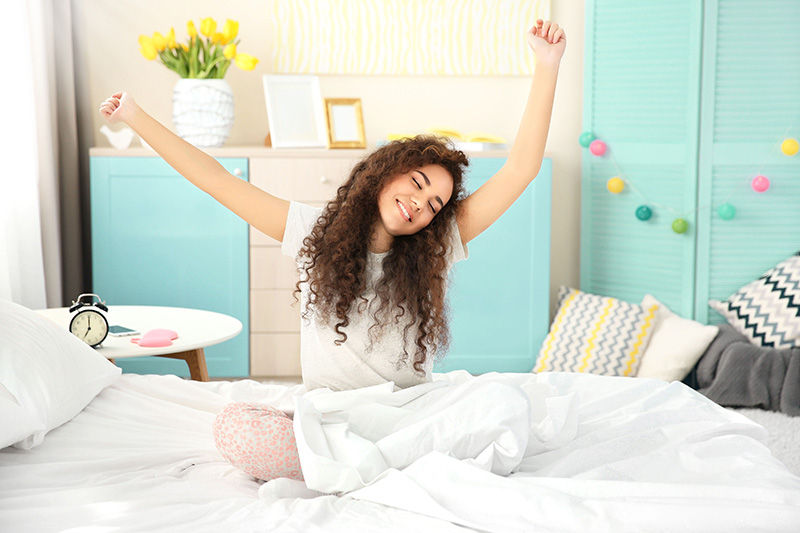Girl stretching in her bed as she wakes up in the morning