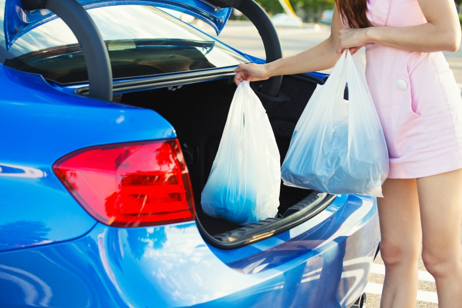 Teen packing up groceries in the trunk of her car