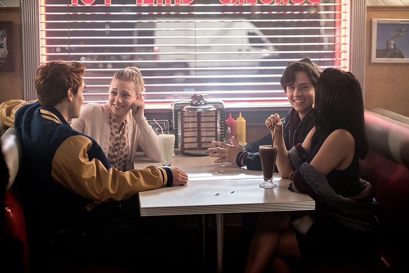 Archie, Betty, Veronica and Jughead sitting in a booth at Pop's Chock'Lit Shoppe