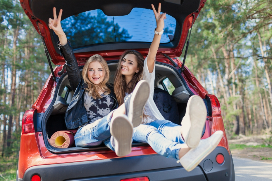 two cute girlfriends flaunt peace signs as they hang out in the back of a car's trunk