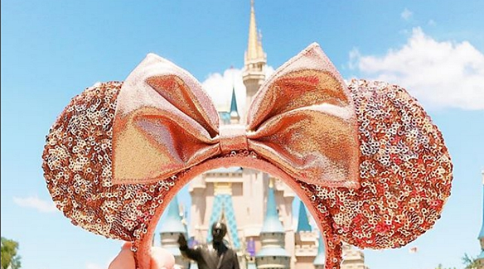 Rose gold Minnie Mouse ears in front of the castle