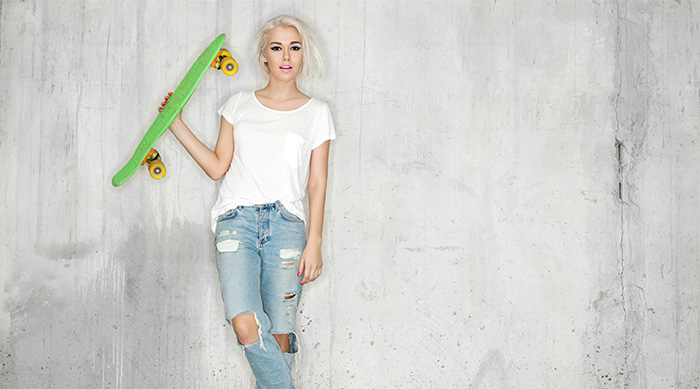 Girl in white t-shirt and ripped jeans holding a skateboard