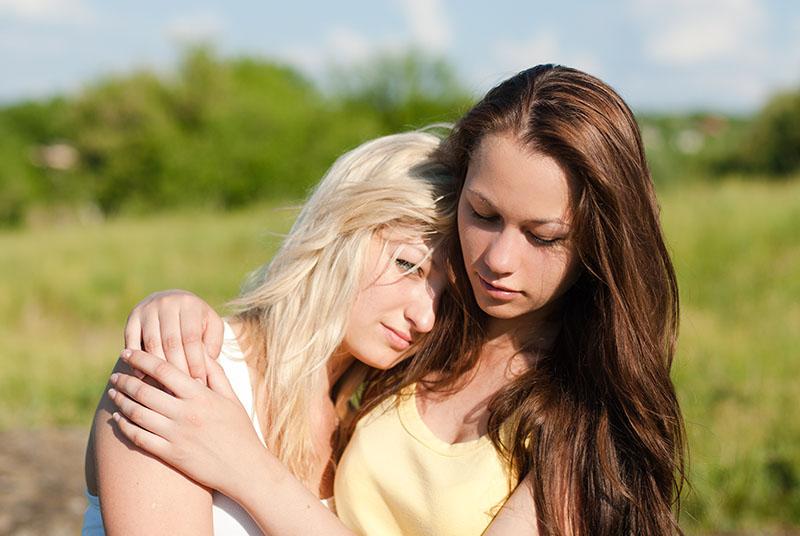 Brunette girl consoling her sad blonde friend