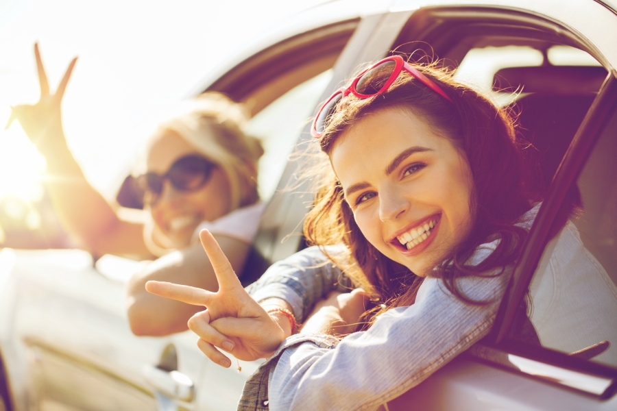 Two friends flashing peace signs in car