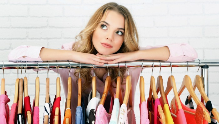 girl leaning on rack of clothes