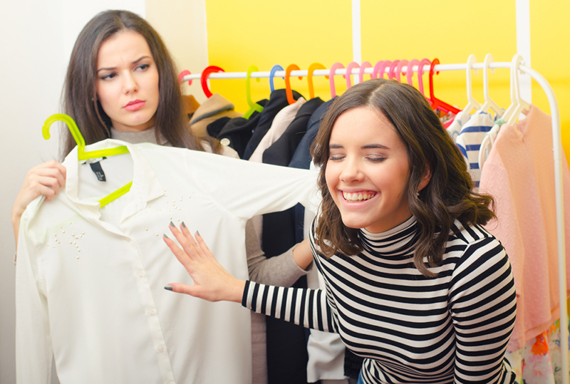 Girl laughing at the shirt her friend wants to buy