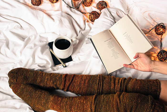 Girl cozy in bed reading book and drinking coffee
