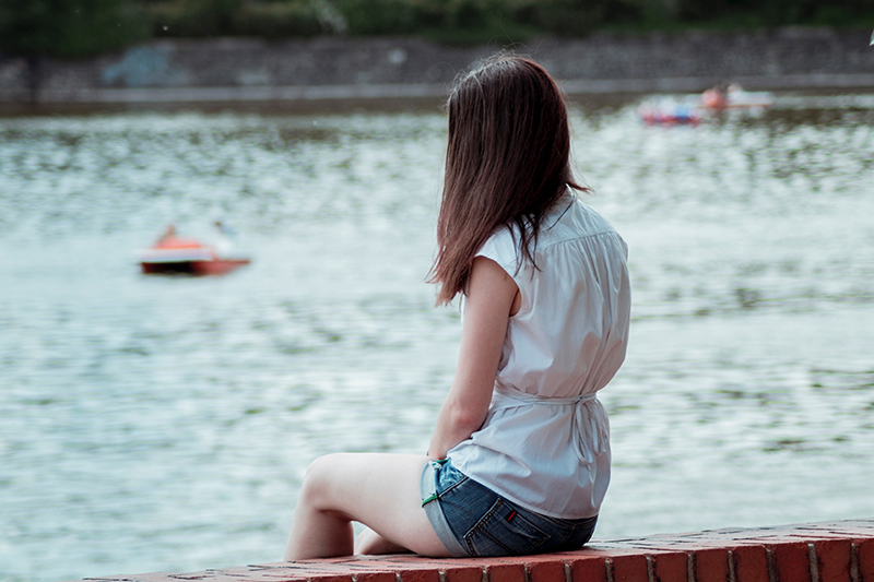 Girl sitting alone on a bench looking out into the water