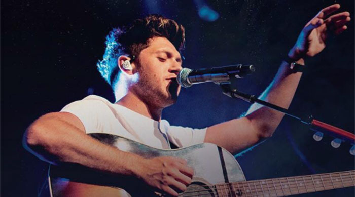 Niall Horan singing into a microphone while playing guitar
