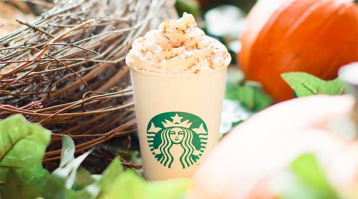 Starbucks' Pumpkin Spice Latte surrounded by pumpkins