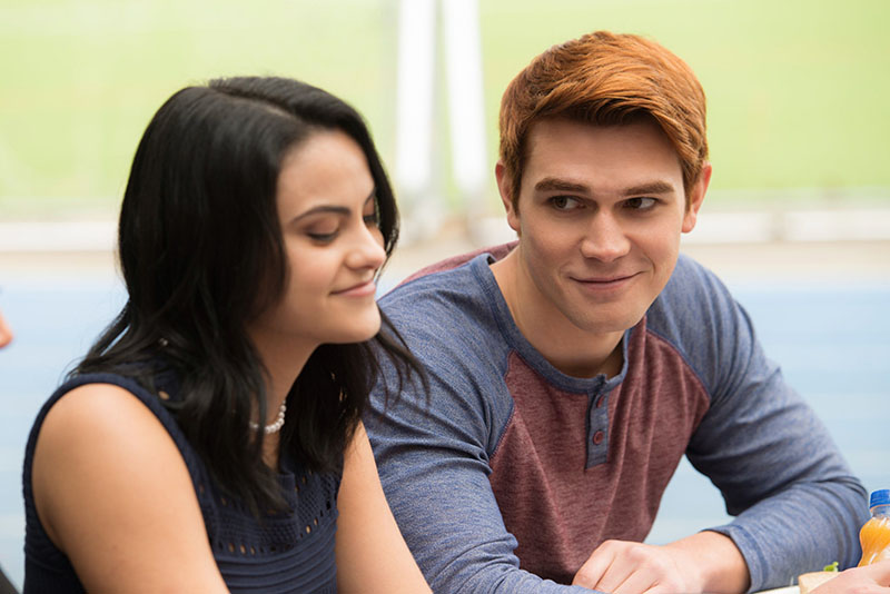 Archie smiling at Veronica while she's talking to Betty on Riverdale
