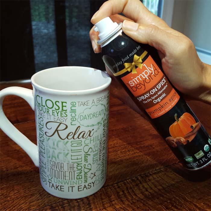 Woman spraying pumpkin spice spray into coffee mug