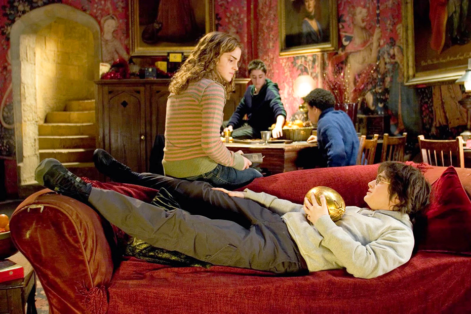 Harry Potter holding a gold egg with Hermione in common room