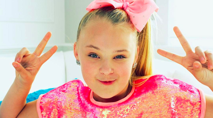 JoJo Siwa holding up peace sign for the camera