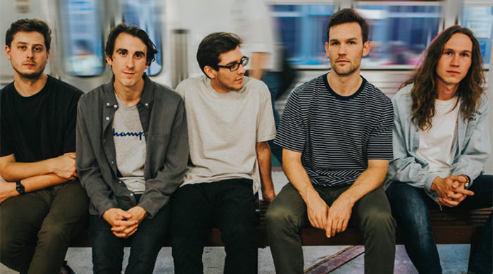 Pop punk band Knuckle Puck sitting on a bench waiting for a train