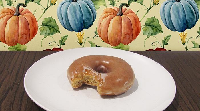 Krispy Kreme pumpkin spice original glazed donut with bite