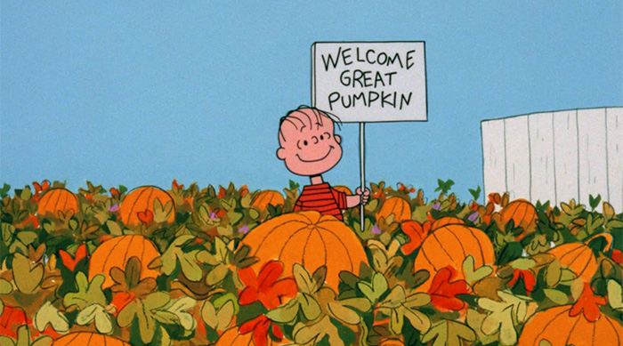 "Linus holding a ""Welcome Great Pumpkin"" sign in the middle of a pumpkin patch"