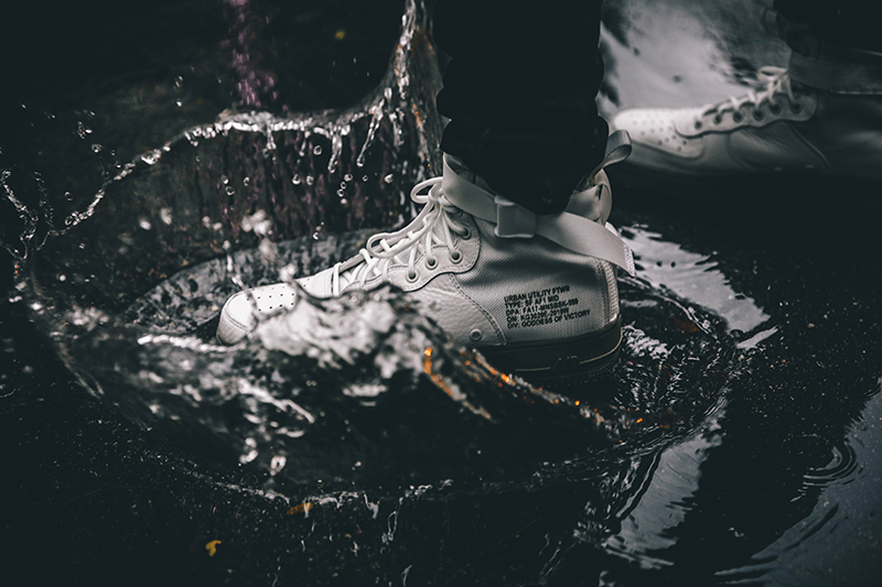 Guy wearing white sneakers jumping into a puddle
