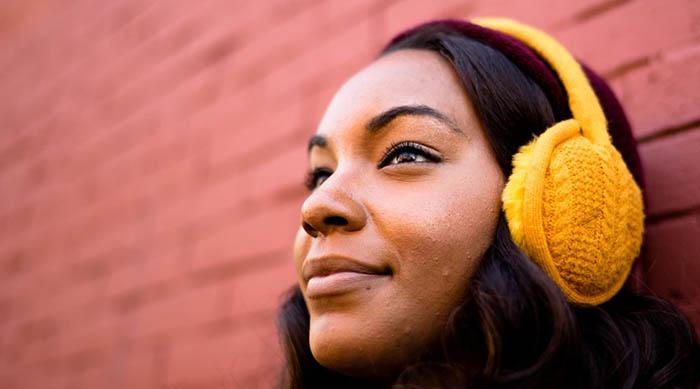 Woman against a brick wall wearing orange Sound Huggle headphones