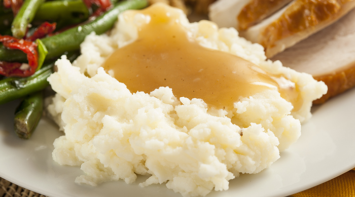 Mashed potatoes and gravy on a plate with green bean casserole and turkey for Thanksgiving dinner