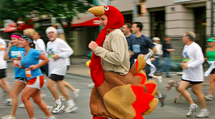 Man dressed up as a turkey running in a Turkey Trot on Thanksgiving